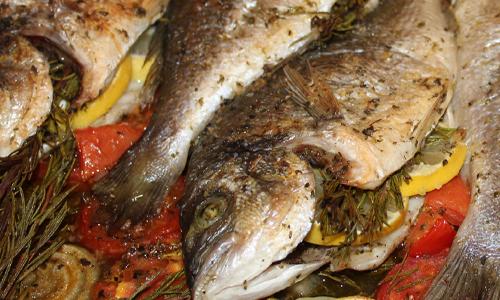 Dorade im Ofen mit Gemüse gefüllt mit Rosmarin und Zitrone.